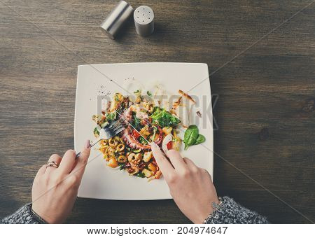 Eating salad with octopus and vegetables top view. Unrecognizable person dining on appetizing fresh mediterranean seafood meal with toasts in restaurant