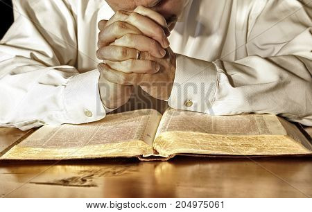 A married man in a white long-sleeved shirt bows his head and has his hands clasped in deep prayer over his Holy Bible.