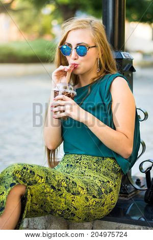 Fashionable Girl Sitting On The Street With Coffee To Go