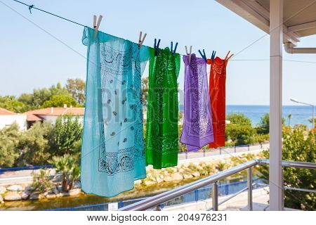 Four Colored Bandanas Hang On A Rope In The Street Overlooking The Sea