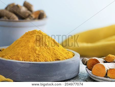 selective focus shot of powdered turmeric in a pile place in a blue clay ceramic dish with raw root a light background copy space at header and side