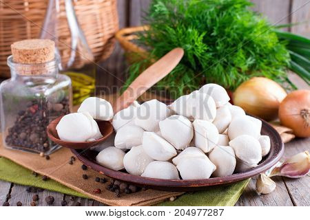 Small frozen dumplings in brown plate on wooden table. Homemade ravioli. Russian dumplings. Pelmeni