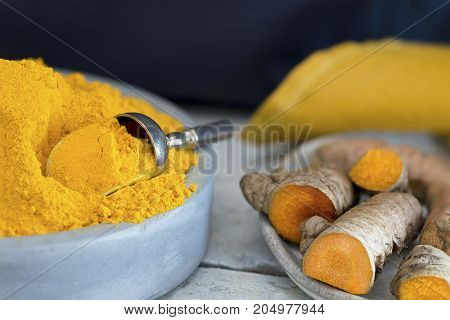 macro of turmeric spice in a blue clay bowl with with the raw roots to the side on a dark background copy space at the head of image