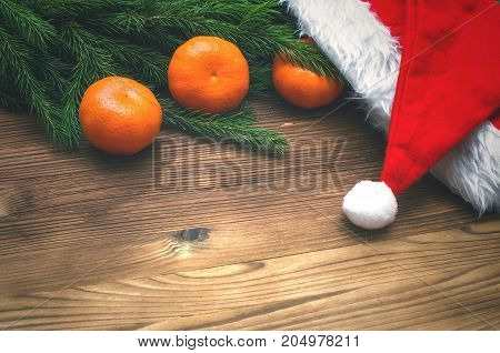 Tangerines christmas tree branches and Santa Claus hat on burnt wooden surface background with copy space. Christmas new year background.