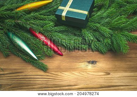 Christmas present box in fir tree branches with toy icicles around on burnt wooden board surface background with copy space. Christmas decorations.