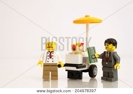 Colorado, USA - September 19, 2017: Studio shot of LEGO businessman hot dog seller with customer ready to buy, isolated on white background.