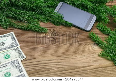 Mobile phone and money dollars laying in fir tree branches on burnt wooden board surface background with copy space. Christmas decorations.
