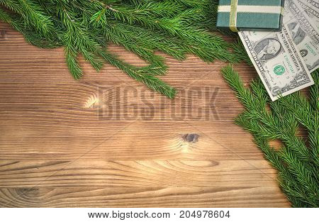 Present box with money inside laying in Christmas fir tree branches on burnt wooden board surface background with copy space. Christmas decorations.