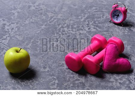 Dumbbells In Pink Color Next To Apple, Alarm Clock, Heart
