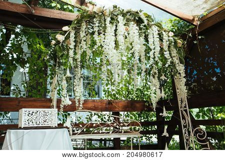 Wedding arch decorated with white hanging flowers