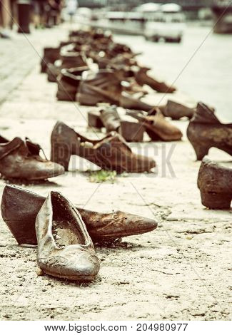 Shoes monument on the Danube bank is a memorial in Budapest Hungary. Place of reverence. Symbolic object. Retro photo filter.