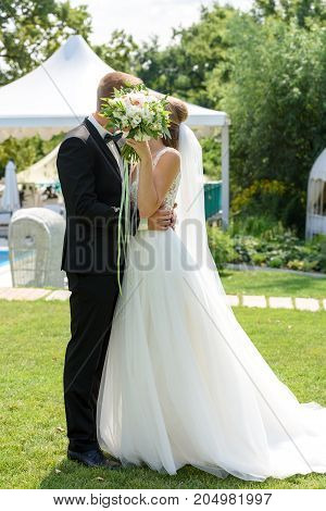 Happy bride and groom with bridal bouquet kissing in park on summer wedding day. Kissing wedding couple in love newlyweds free space. Bride and groom on nature