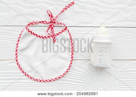 children feeding with breastmilk or infant formula powdered baby milk and bib on wooden white table background top view space for text