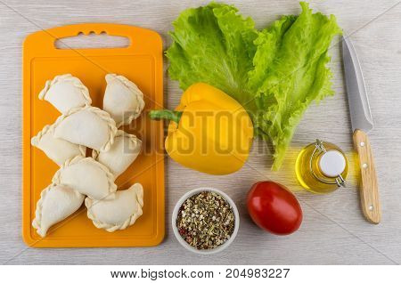 Frozen Dumplings On Cutting Board, Condiment, Oil, Vegetables And Knife