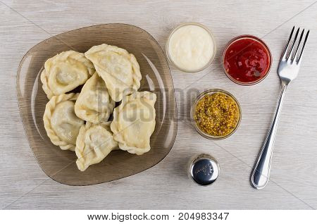 Boiled Dumplings, Bowls With Ketchup, Mustard, Horseradish. Pepper And Fork