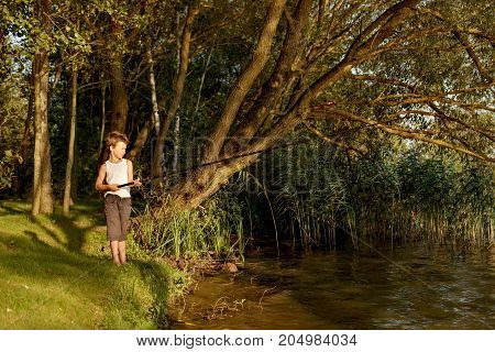 a young boy is fishing in a river