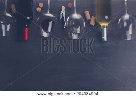 Bottles of red and white wine with wine glasses on table with copy space, retro toned