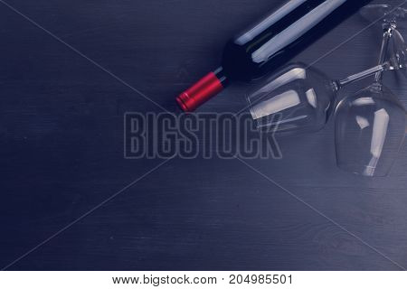 Bottle of red wine and two wine glasses on table with copy space, retro toned
