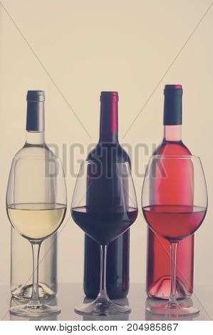 Set of three wine glasses and bottles with red, white and rose wine, retro toned