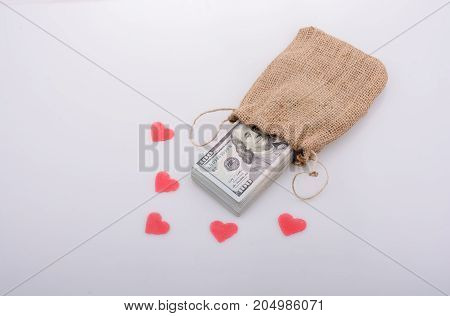 Red hearts and banknote bundle of US dollarin a sack