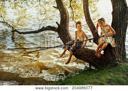 naughty boy and girl sitting on a branch over water fishing, laughing, having fun talking