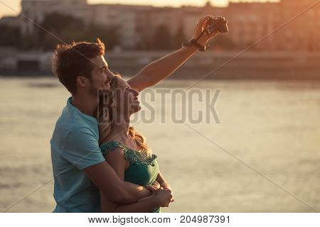 Young happy couple taking selfie with camera.