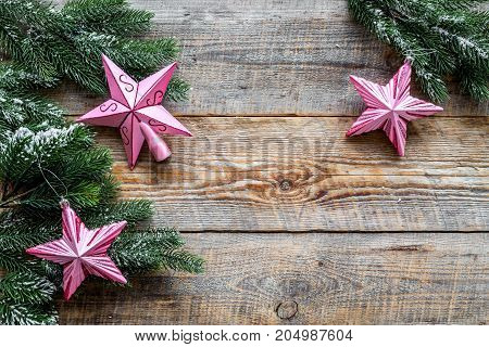 Christmas toys. Pink stars near pine branches on wooden background top view.