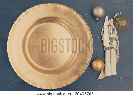 Christmas empty golden plate with knife and fork, top view, retro toned