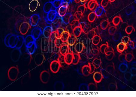 Abstract background of colorful circles in motion on black. Bokeh of defocused curls, blurred neon blue and red leds, glowing festive backdrop of night city lights