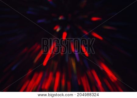 Abstract background of colorful lines in motion on black. Bokeh of defocused splashes, blurred red and violet neon leds, fireworks and salute, space and sky backdrop