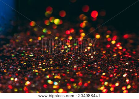 Abstract shining glitters golden holiday bokeh background with copy space. Defocused lights backdrop, selective focus with shallow depth of field. Christmas and New Year wallpaper decorations concept