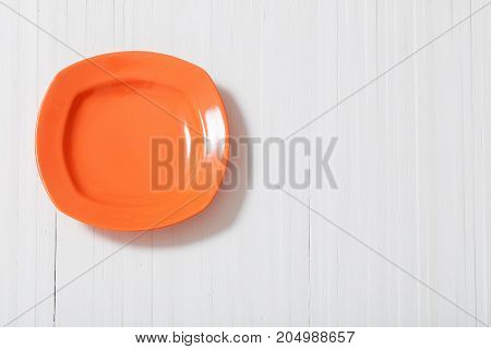 the orange plate on white wooden background