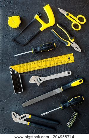 constructor desk pattern with set of building implements on dark desk background top view