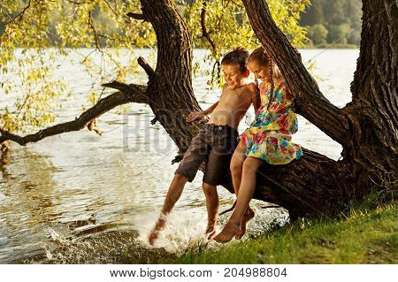 naughty boy and girl sitting on a branch over water, laughing, having fun talking and splashing