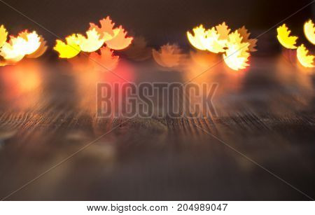 Autumn maple leaf bokeh on wooden background.
