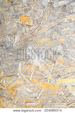 Weather damaged Oriented Strand Board. Construction material. OSB wooden panel made of pressed sandy brown wood shavings as background closeup