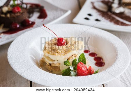 Presentation of delicious desserts in restaurant. napoleon and chocolate cake serving on wooden table, close up picture