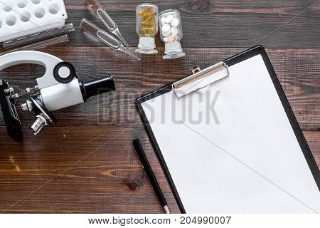 Doctor's workplace. Microscope, pills, tablet, ampoulie on wooden background top view