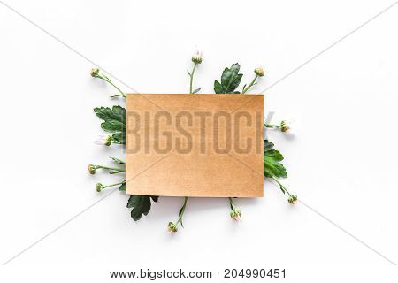 Floral mockup. Notebook among buds and leaves on white background top view.