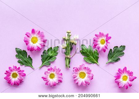 Floral pattern with pink flowers and green leaves on purple background top view.