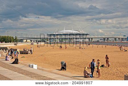 SAINT - PETERSBURG, RUSSIA - AUGUST 16, 2017: People on the beach in the 300 years St. Petersburg Anniversary Park. On the background is Krestovsky Stadium (Zenit Arena) by Kisho Kurokawa