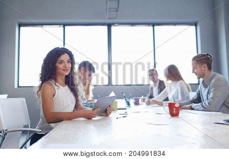 Attractive woman sitting at the table on a business meeting on a conference room background. Office people working together. Copy space.