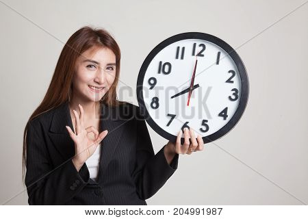 Young Asian Woman Show Ok With A Clock.