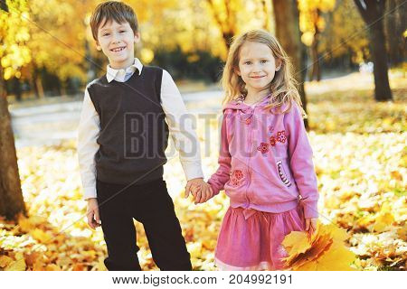 happy schoolboy and little girl stand holding each other's hands, laughing and playing in the autumn on the nature walk outdoors