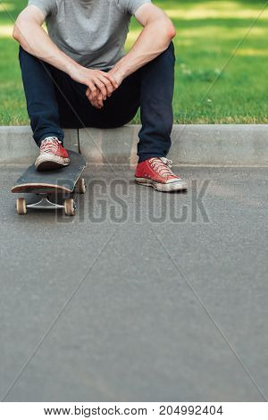 Unrecognizable hipster man with skateboard, extreme sport challenge and competition background with free space. Skateboarder modern urban lifestyle and culture, ready to adventure