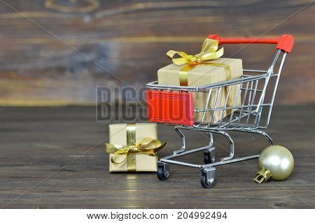 Christmas shopping cart with gift boxes on wooden background