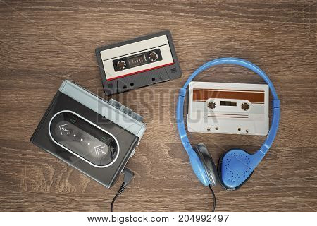 Vintage cassete and headphones on the wooden background