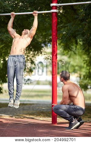 Two sporty friends exercising on horizontal bars on a blurred urban background. Two hot, shirtless and athletic men.
