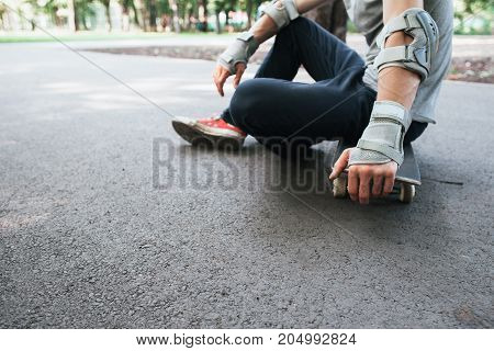 Unrecognizable skater takes breath after training. Extreme sport challenge and competition, skateboarder equipment and urban sportive lifestyle background with free space