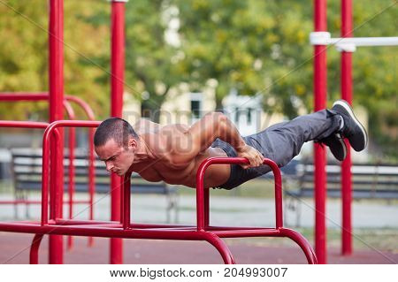 Muscular young man standing on strong hands on horizontal bars on a blurred park background. Shirtless hot sportsman working out.